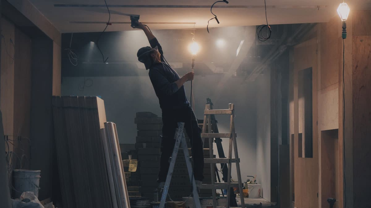 Man on a latter installing lighting fixture
