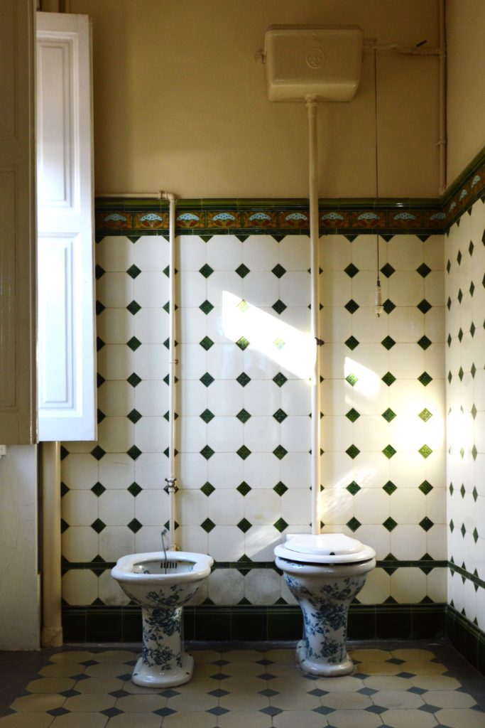 Bidet and toilet in a bathroom with white/black patterned tile wall and floor