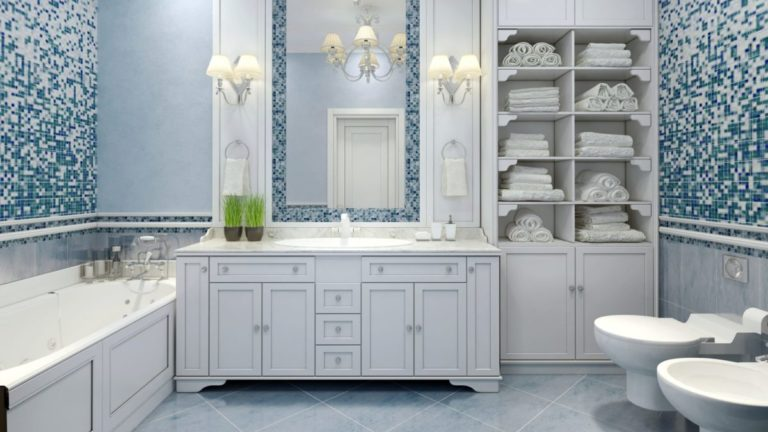 white and blue bathroom with mosaic tile, white furniture, toilet and bidet, tub, chandelier, furniture-style vanity