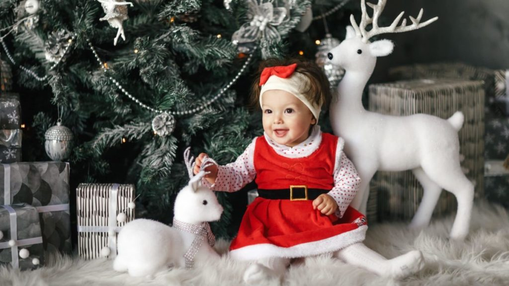 Baby girl in santa dress and hat in front of Christmas tree with silver decorations and white dear statues.