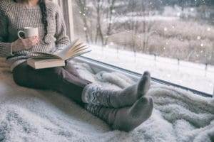 Woman in sweater, leggings, and cozy socks reading by a large window with snow outside